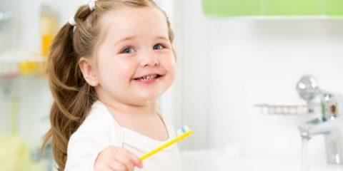 21965611 – smiling child girl brushing teeth in bathroom
